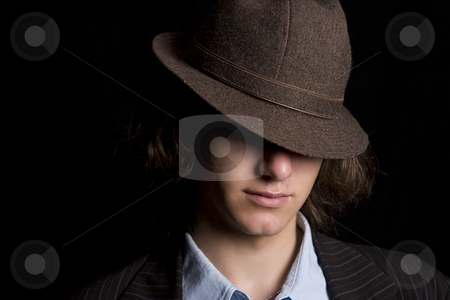 Hidding under a hat stock photo, Male teenager with a hat tipped over the eyes by Yann Poirier