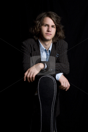 Leaning on instrument case stock photo, portrait of a male teenager wearing a suit leaning on a instrument case by Yann Poirier