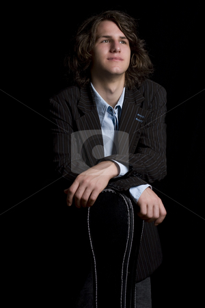 Leaning on instrument case stock photo, Portrait of a male teenager wearing a suit leaning on a instrument case, looking up by Yann Poirier