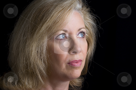 Head shot of a middle age women stock photo, Head shot of a women in her early fifties look off frame to the rigth by Yann Poirier