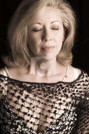 Breath in stock photo, Portrait of a women in her early fifties taking in a deep breath by Yann Poirier