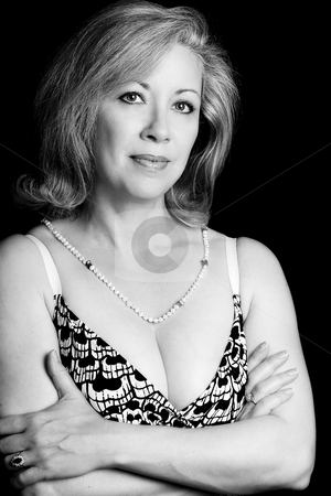 Portrait of a middle age women stock photo, Black and white portrait of a women in her early fifties with her arms folded by Yann Poirier