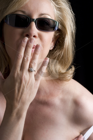 Fashionyta blowing a kiss stock photo, Women in her early fifties wearing sunglass blowing a kiss by Yann Poirier