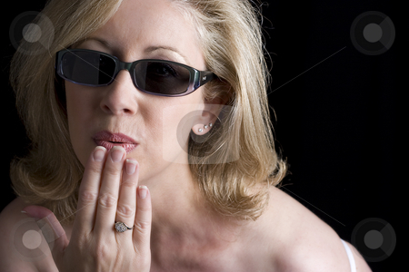 Fashionyta blowing a kiss stock photo, Women in her early fifties wearing sunglass blowing a kiss.  Her left thumb has a bandage due to a paper cut by Yann Poirier