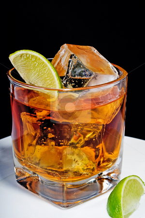 Whiskey in a glass with ice cubes and slices of lime stock photo, Whiskey in a glass with ice cubes and slices of lime by Vincent Demers