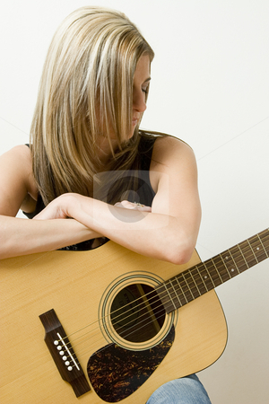 Pondering on music stock photo, Thirty something women leaning on a accoustical guitar by Yann Poirier