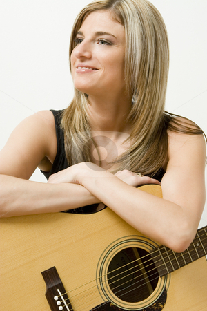 Guitar Player stock photo, Thirty something women leaning on a accoustical guitar by Yann Poirier