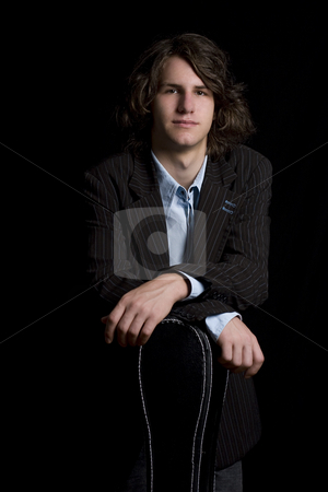 Teen Guitar player stock photo, portrait of a male teenager wearing a suit leaning on a instrument case by Yann Poirier