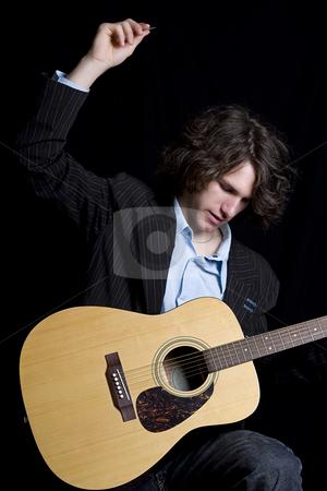 Big strum stock photo, Male teenager folk guitar player about to do a big strum by Yann Poirier