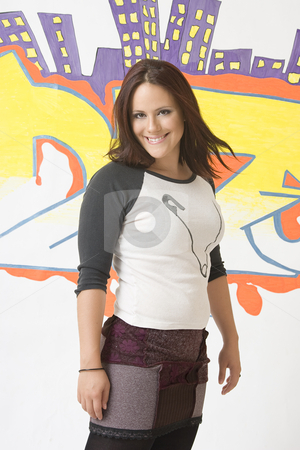 A urban girl smiling stock photo, Teen girl in front of a graffiti with great big smile by Yann Poirier