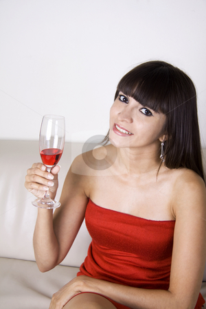 Woman having a drink at a party stock photo, Latina woman in a red dress is having a red drink while sitting on a beige couch by Daniel Kafer
