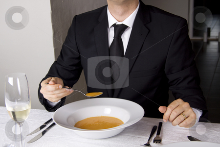Business man is having lunch stock photo, Business man is having lunch at a frensh gourmet restaurant. He is having lobster soup. by Daniel Kafer
