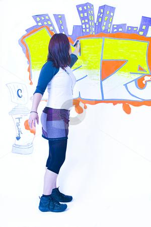 Writting on wall stock photo, Teen girl drawing a graffiti on a wall by Yann Poirier