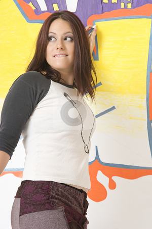 About to be caught stock photo, Teen girl drawing a graffiti on a wall about to be caught and bitting her lower lip by Yann Poirier