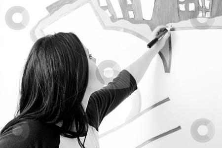 Doing a graffiti stock photo, Teen girl drawing a graffiti on a wall by Yann Poirier