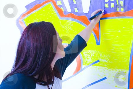 Drawing a graffiti stock photo, Teen girl drawing a graffiti on a wall by Yann Poirier