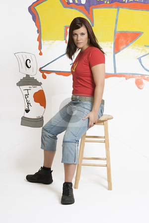 Sitting on stool stock photo, Teen girl sitting on stool in front of graffitied wall by Yann Poirier