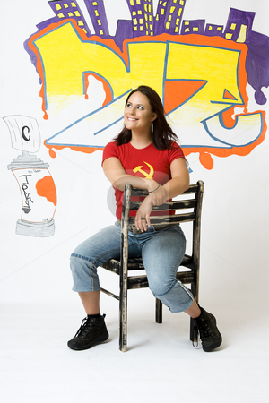 Happy girl stock photo, Young women with great big smile sitting on a ruff up chair in front of a graffiti background by Yann Poirier