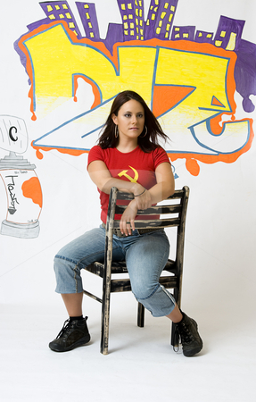 Concentration stock photo, Young women with an intense look sitting on a ruff up chair in front of a graffiti background by Yann Poirier