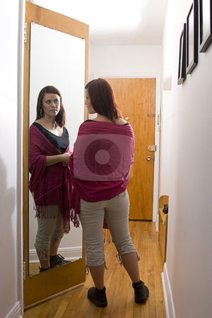 A mirror in the corridor stock photo, Young woman standing in front of mirror by Yann Poirier