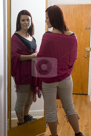 Women in front of mirror stock photo, Young woman standing in front of mirror adjusting shawl by Yann Poirier