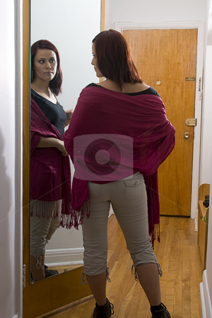 Adjusting clothes stock photo, Young women adjusting her clothing in front of a mirror in the corridor of an appartment by Yann Poirier