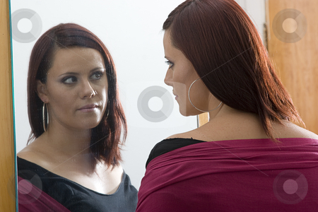Admiring reflection stock photo, Young women looking at her reflection in a mirror by Yann Poirier