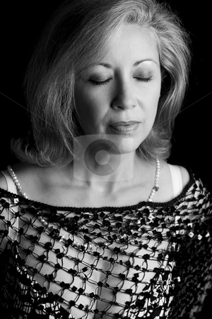 Women in her fifties in black and white stock photo, Portrait of a women in her fifties, with her eyes close, in black and white by Yann Poirier