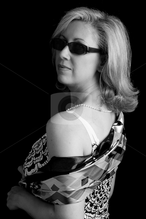 Fashionyta looking over her shoulder stock photo, Black and white portrait of a women in her early fifties with classic Audrey Hepburn looking over here shoulder by Yann Poirier
