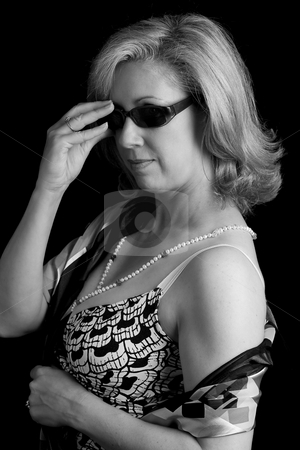 Fashionyta taking her sunglass off stock photo, Black and white portrait of a women in her early fifties with classic Audrey Hepburn taking her sunglass off by Yann Poirier