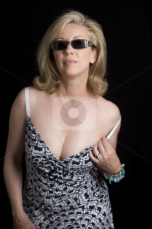 Fashionyta adjusting her dress stock photo, Women in her early fifties wearing sunglass adjusting the strap of her dress by Yann Poirier