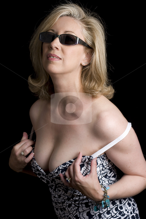 Fashionyta undressing stock photo, Women in her early fifties wearing sunglass starting to take off her dress by Yann Poirier