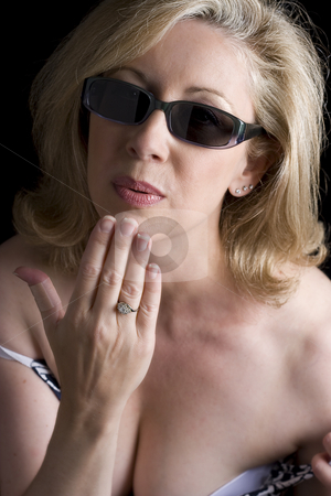 Blowing a kiss stock photo, Women in her early fifties wearing sunglass blowing a kiss.  Her left thumb has a bandage due to a paper cut by Yann Poirier