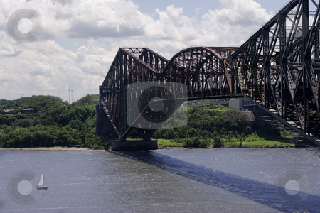 Metal bridge stock photo, Quebec old metal bridge with sail boat passing under by Yann Poirier