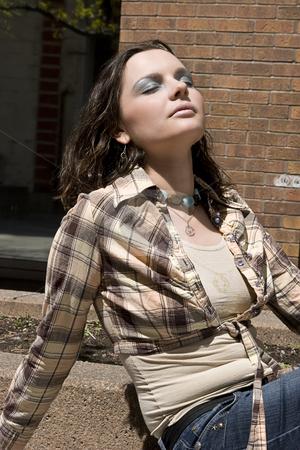 Urban sun tanning stock photo, Teen girl enjoying the sun in an urban setting by Yann Poirier