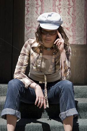 Sitting on stair stock photo, Teen girl sitting on stair of a front porch, adjusting her sunglasses by Yann Poirier