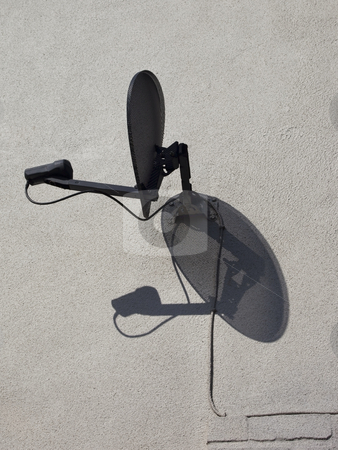 Black satellite dish stock photo, A black satellite dish on a white textured wall with shadow by Mike Smith