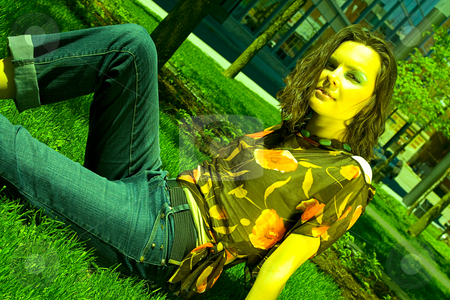 Sitting in the grass stock photo, Teenage girl sitting in a park on the grass under the noon sun by Yann Poirier