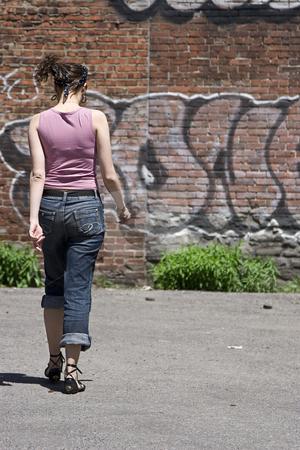 Walking away stock photo, Teenage girl walking away in a parking lot, heading towards a brick wall with graffiti by Yann Poirier