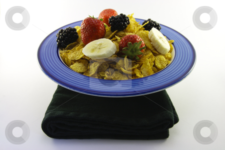 Cornflakes and Fruit in a Bowl with Napkin stock photo, Cornflakes with strawberries, blackberries and banana in a round blue bowl with a black napkin on a white background by Keith Wilson
