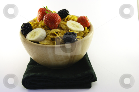 Cornflakes and Fruit in a Bowl with Napkin stock photo, Cornflakes with strawberries, blackberries and banana in a round wooden bowl on a white background by Keith Wilson
