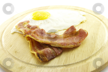 Bacon and Eggs on Wooden Plate stock photo, Slices of crispy pork bacon and a fried egg on a wooden round plate with a white background by Keith Wilson