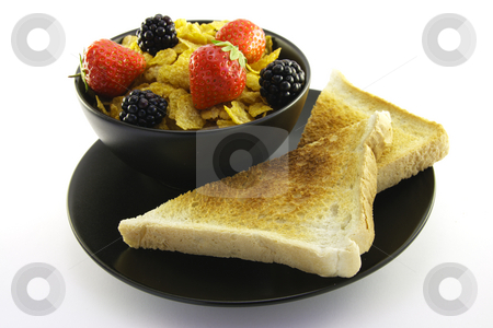 Cornflakes in a Black Bowl with Toast stock photo, Cornflakes with strawberries and blackberries in a round black bowl with a slice of toast on a white background by Keith Wilson