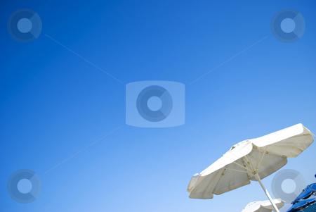 Umbrella on beach stock photo, White and blue umbrellas on sunny beach by Desislava Dimitrova