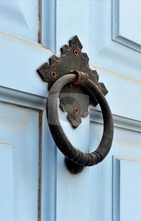 Door knocker stock photo, An old weathered door knocker from a light blue painted wooden door by Andreas Karelias