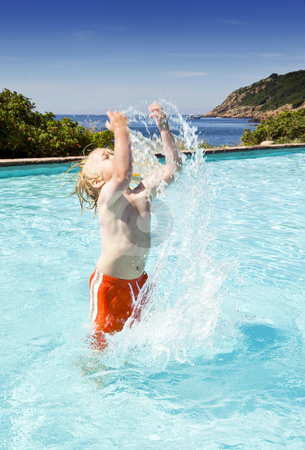 Splashing water stock photo, Young boy in an outdoor pool near the sea splashing water by Corepics VOF