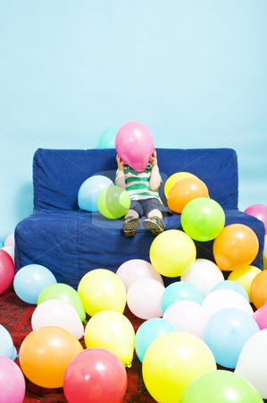 Balloon boy stock photo, Young boy sitting on a couch, hiding behind a pink baloon he's holding by Corepics VOF