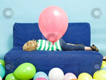 Birthday blues stock photo, Young Boy lying down on a couch on his birthday by Corepics VOF