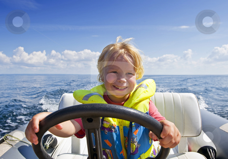 Young helmsman stock photo, Young boy behind the steering wheel of an inflatable speedboat by Corepics VOF