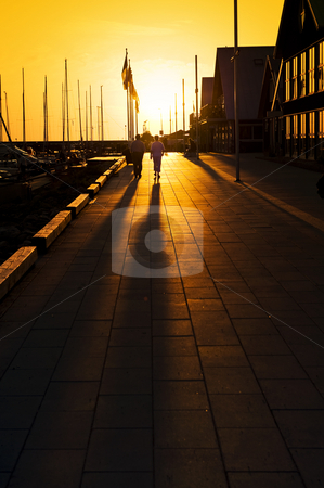 Summer promenade stock photo, Long shadows on a marina promenade on a summer evening by Corepics VOF